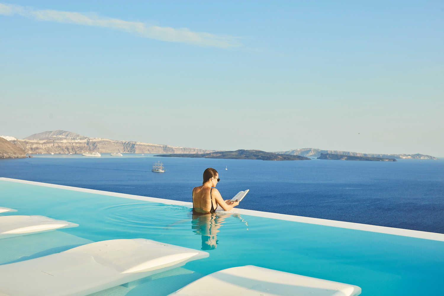 canaves oia suites, woman looking out over infinity pool