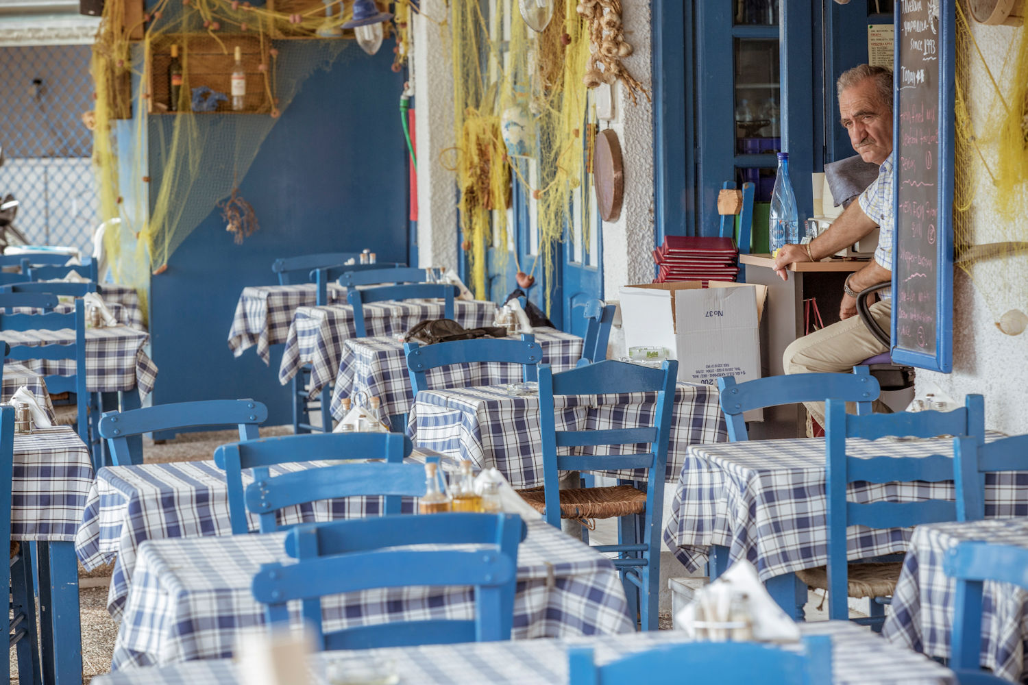 Traditional Greek Taverna with owner looking out from doorway
